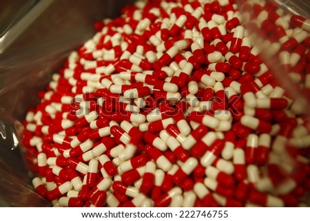 Red and white capsules pills drug production line, tablets coming out of the machine - stock photo
