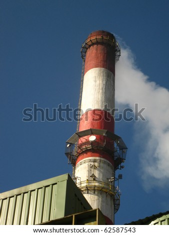 red and white chimney with outgoing exhaust gases or steam