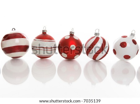 Red and white Christmas baubles with various designs on a white background. - stock photo