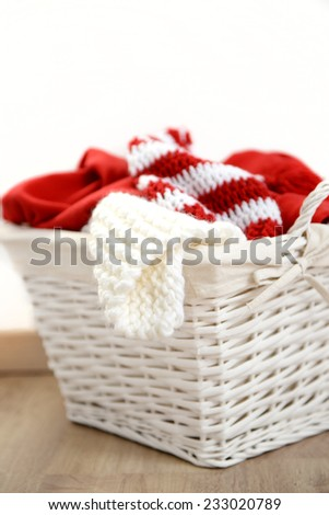 Red and white Christmas clothes in a wicker basket, isolated on white - stock photo