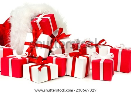 Red and white Christmas gift boxes spilling from a Santa bag over a white background - stock photo