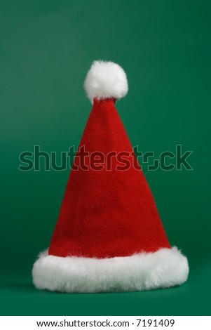 Red and white christmas hat on green background