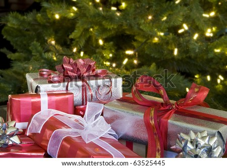 red and white christmas presents with bows by tree