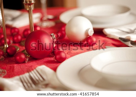 Red and white Christmas table setting, shallow depth of field, focus on ornament - stock photo