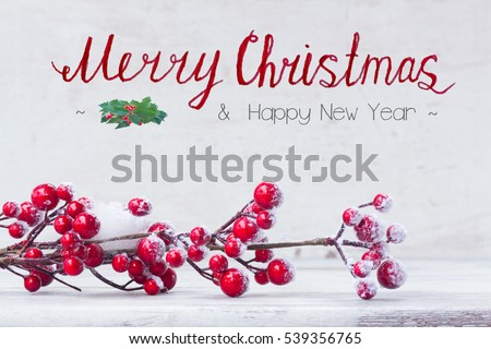 red and white christmas - twig with iced berries on aged wooden background with merry christmas greetings