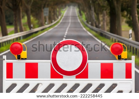 Red and white colored street barrier at an empty road/Closed Road - stock photo
