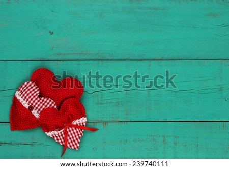 Red and white country fabric hearts collage border on antique teal blue wooden background - stock photo