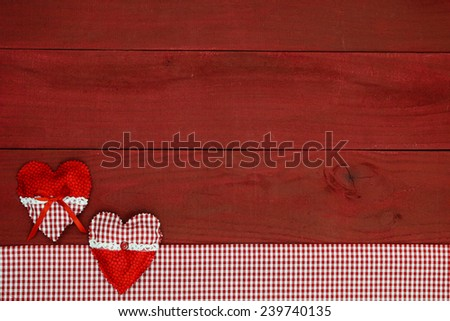Red and white country hearts and gingham fabric border on antique wooden background - stock photo