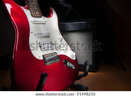 red and white electric guitar and combo amplifier on black background - stock photo