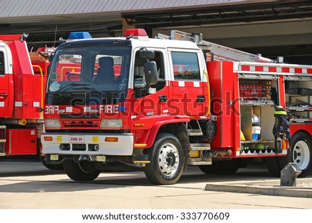 red and white fire trucks ready for action on a high fire danger day - stock photo
