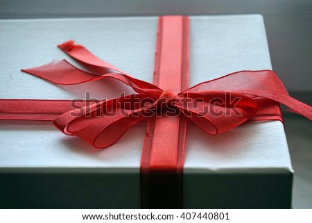 Red and white gift box with a scarlet ribbon on the top in a shape of great topknot  - stock photo