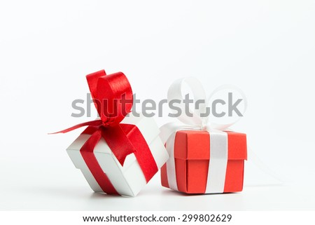 Red and white gift boxes with ribbon over white background - stock photo