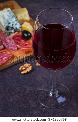 Red and white  glass and bottle of wine. Cheese,  prosciutto, salami, rosemary, nuts, olives and bread on dark rustic wooden background - stock photo