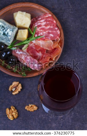 Red and white  glass and bottle of wine. Cheese,  prosciutto, salami, rosemary, nuts, olives and bread on dark rustic wooden background. View from above, top studio shot - stock photo