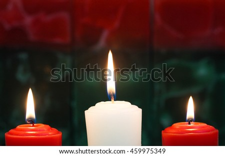 Red and white holiday candles with red and green texture background; Christmas and spiritual concept - stock photo