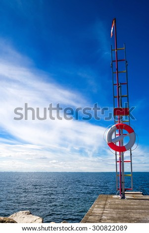Red and White Life Buoy on Seashore of Coastal Summer Vacation Resort - stock photo