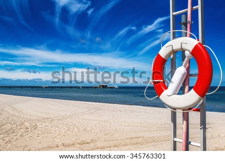 Red and white lifebuoy, lifesaver on sandy beach of coastal summer vacation resort - stock photo