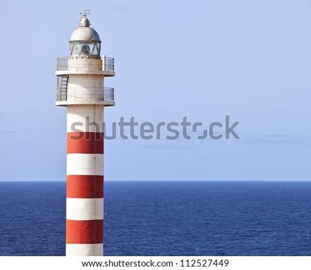 Red and white lighthouse, Faro de Punta Sardina in Gran Canaria, Spain - stock photo