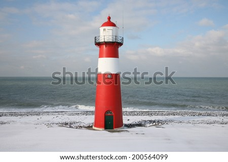 Red and white lighthouse in the snow on a dike - stock photo