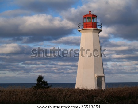 Red and white lighthouse on Prince Edward Island, Canada. - stock photo