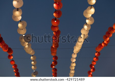 Red and white lights and decorations over blue evening sky in the amusement park. - stock photo