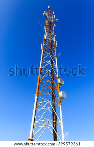 Red and white mast with communication antennas on blue sky background - stock photo