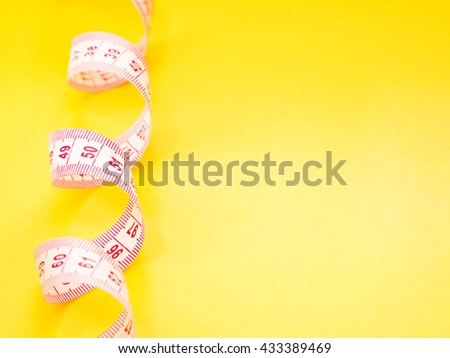 Red and white measuring tape on yellow background - stock photo