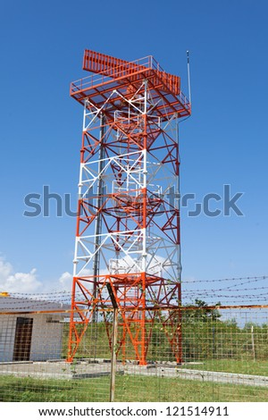 Red and white metal radar tower in airport area - stock photo