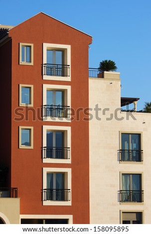 Red and white modern residental building with blue sky - stock photo