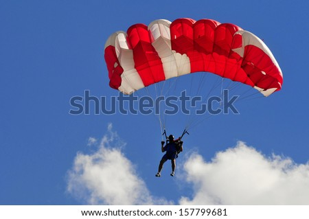 red and White parachute on blue sky with white cloud.