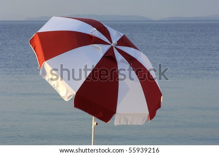 red and white parasol on the beach - stock photo