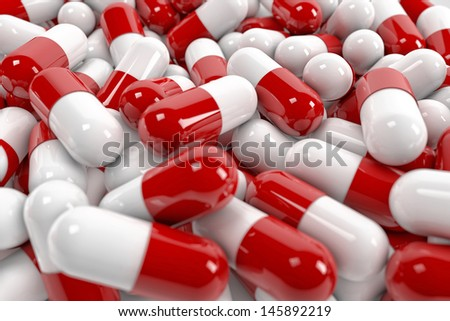 Red and white pill capsules pile - stock photo