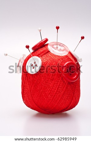 red and white pins in red wool ball with buttons - stock photo