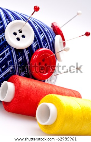 red and white pins in wool ball with buttons - stock photo