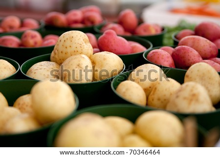 Red and white potatoes in containers at a farmers market. - stock photo