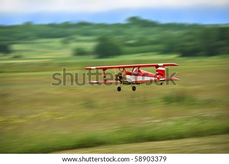 Red and white radio controlled aircraft with methanol engine flying over grassy field. The image shows motion blur. - stock photo