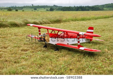 Red and white radio controlled aircraft with methanol engine on a grassy field. - stock photo