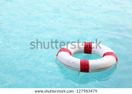 red and white rescue wheel on swimming pool - stock photo