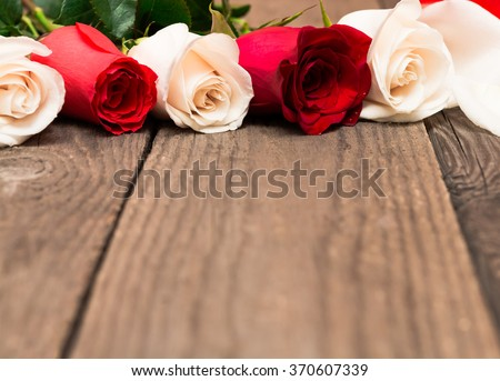 Red and white roses on wooden background. Women' s day, Valentines Day, Mothers day. Copy space, selective focus. Natural optical blur.