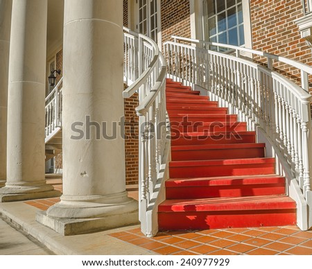 Red and white stairway behind concrete building columns. - stock photo