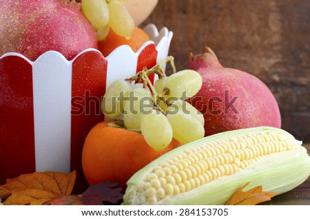 Red and white stripe bowl with Autumn Harvest fruit and vegetables on dark vintage wood background, close up.   - stock photo