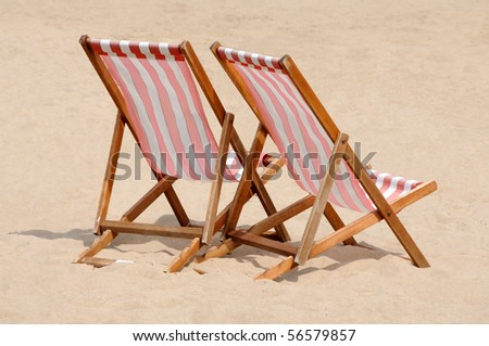 Red and white striped deckchairs on a British beach - stock photo