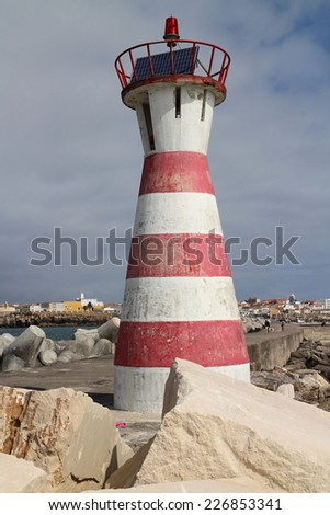 Red and white striped lighthouse on wharf of Peniche, Portugal - stock photo