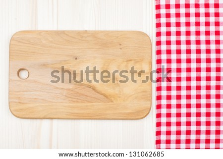 Red and white tablecloth, kitchen plank on wood table background - stock photo