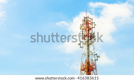 red and white telecommunication tower on blue sky background - stock photo