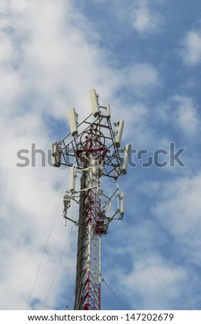 Red and White Telecommunication tower with blue sky and cloud