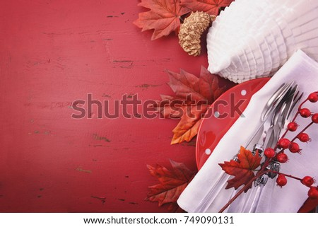 Red and white theme Thanksgiving background with decorated borders on a distressed red wood table, with a white turkey tureen and table setting, with applied filters.
