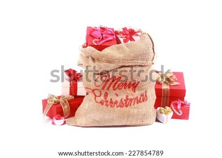 Red and white themed Santa Gift Sack with a rustic hessian sack with Merry Christmas greeting filled to overflowing with red and white wrapped gift boxes tied with ribbon, over white - stock photo