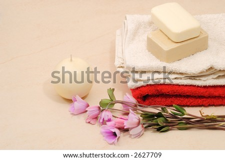 red and white towels and honey soaps with candle in spa bathroom (spa concept )