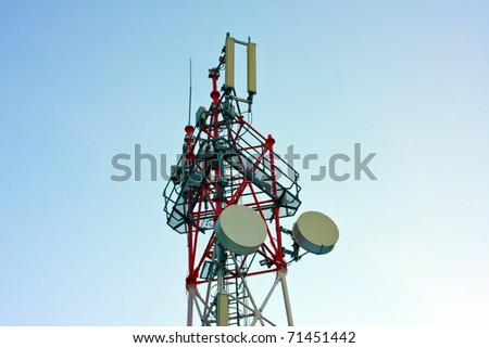 Red and white tower of communications with a lot of antennas under clear sky. - stock photo